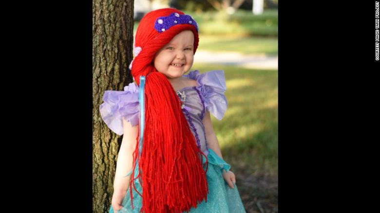 Violet is 2½ years old. Over the summer, she was diagnosed with acute lymphoblastic leukemia. Her mother discovered the Magic Yarn Project right as Violet was losing her hair. Now, she enjoys wearing an Ariel wig with her matching dress.