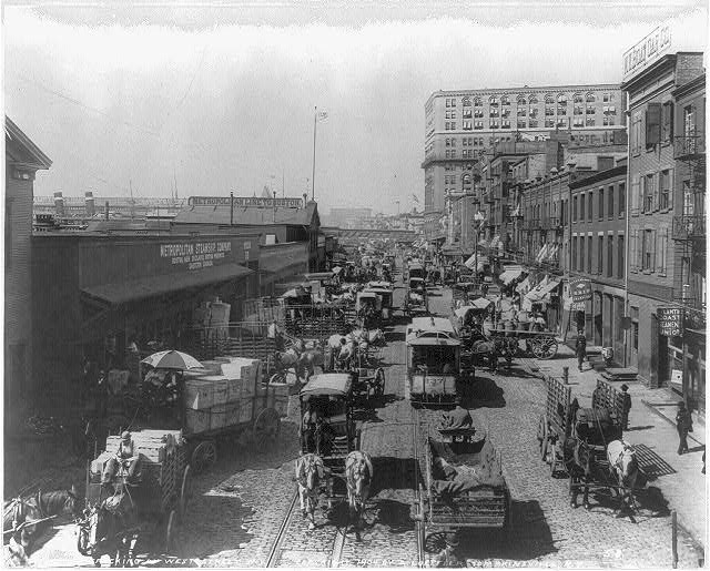 [New York City. View along waterfront on West Street; many freight wagons; street car]