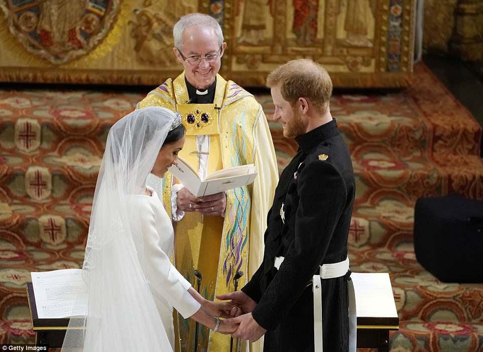 El arzobispo de Canterbury sonríe mientras el príncipe Harry y Meghan Markle se paran en el altar de la Capilla de San Jorge