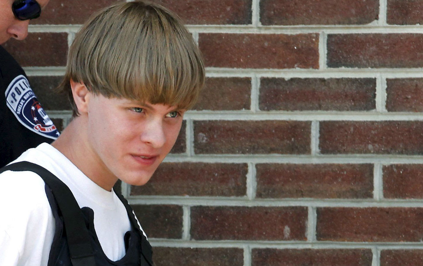 Police lead suspected shooter Dylann Roof, 21, into the courthouse in Shelby, North Carolina, June 18, 2015. Roof, a 21-year-old with a criminal record, is accused of killing nine people at a Bible-study meeting in a historic African-American church in Charleston, South Carolina.