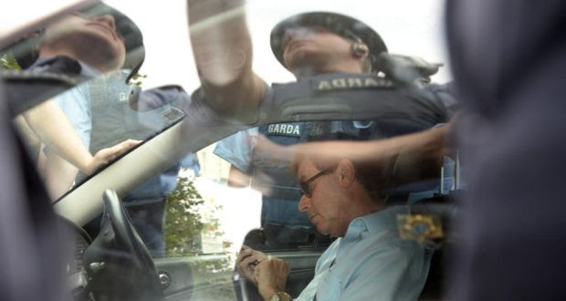 Alan Shatter using his phone as gardaí surround his car. Photograph: Dara Mac Dónaill / The Irish Times