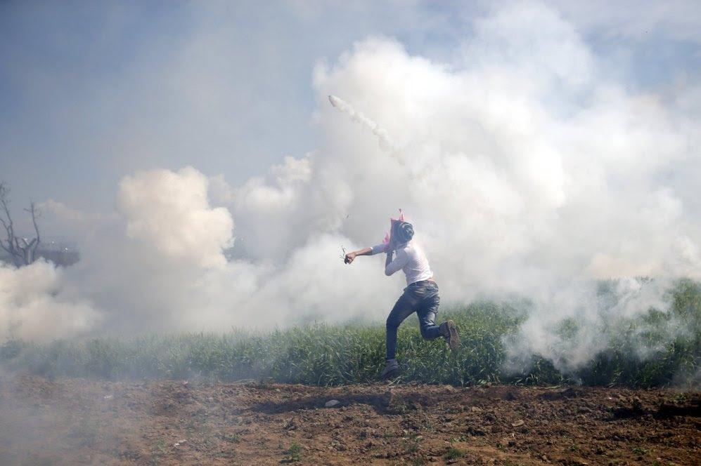 Un migrante devuelve un bote de gas lagrimógeno.