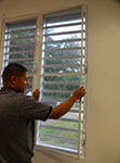 man applying screens to window