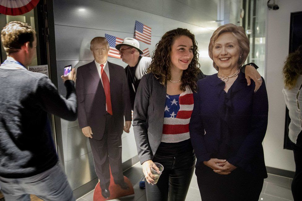 Visitors take a selfie with portraits of presidential candidates Hillary Clinton and Donald Trum