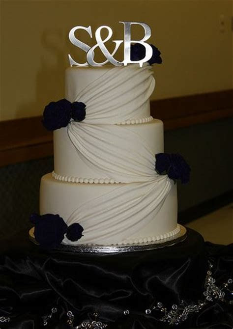 Three tier ivory wedding cake with silver monogram topper