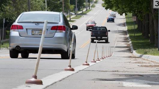 Omaha cyclists use toilet plungers to create a DIY bike lane