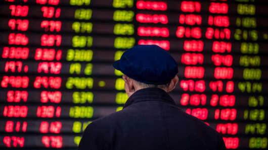An investor looks at an electronic board showing stock information at a brokerage house in Shanghai on March 16, 2017.