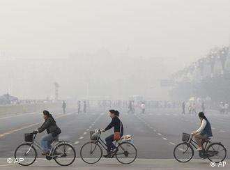 ** FILE ** Chinese cycle through smog and pollution over Beijing's Tiananmen Square Thursday , May 1, 2008. Beijing's Olympic shutdown begins Sunday, July 20, 2008, a drastic plan to lift the Chinese capital's gray shroud of pollution just three weeks ahead of the games.(AP Photo/Oded Balilty) Creation Date:    5/1/2008 14:10:09 China_Olympia_FRA107.jpg