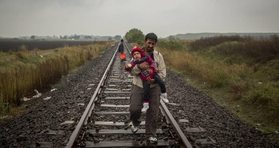 Un padre camina por las vías del tren con su hijo en brazos después de cruzar la frontera entre Serbia y Hungría (Roszke, Hungría, septiembre de 2015).