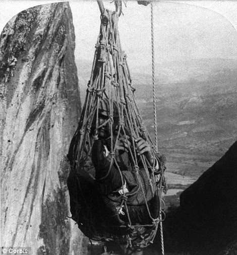 A man is hoisted up 250ft in a cargo net to the Monastery of St Barlaam, which is the only way to access the building