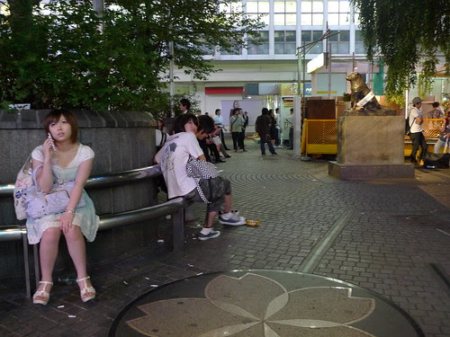 Hachiko statue from afar (and a chick talking on the phone sitting in foreground)