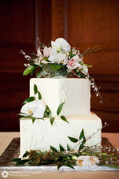 Two tiered square wedding cake with floral cake topper