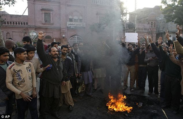 People protest outside a police station in Lahore following the killing of the motorcyclists