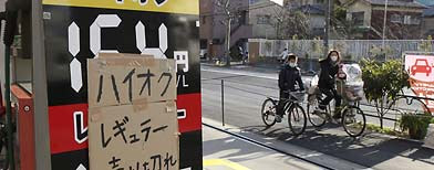 A sold-out note is pasted on a gas price board as bicyclers pass by a gas station in Tokyo, Wednesday, March 16, 2011.