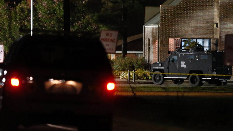 Police drive past the Tensas State Bank branch in St. Joseph, La., early morning, Aug. 14, 2013 in St. Joseph, La., where a gunman took three people hostage.