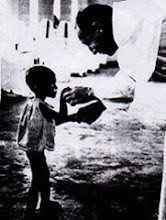 A starved Biafran child fed by a priest