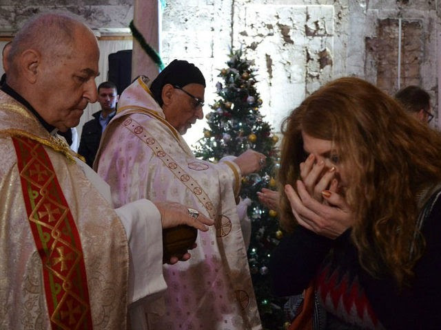 n Iraqi receives the Eucharist during a Christmas mass at the Saint Paul's church on December 24, 2017 in the country's second city Mosul. Hymns filled a church as worshippers celebrated Christmas for the first time in four years after the end of jihadist rule. Tens of thousands of Christians fled northern Iraqi towns in 2014 as the Islamic State group seized Mosul and swathes of the surrounding Nineveh province. / AFP PHOTO / Ahmad MUWAFAQ (Photo credit should read AHMAD MUWAFAQ/AFP/Getty Images)