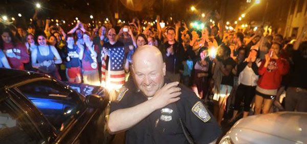 Upon hearing that the second Boston Marathon bombing suspect was taken into custody, a police officer grins while the crowd cheers behind him in a Boston suburb...on April 19, 2013.