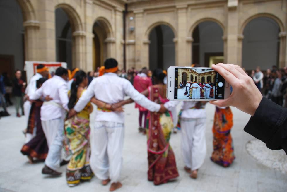 Una espectadora graba a los bailarines adivasis.