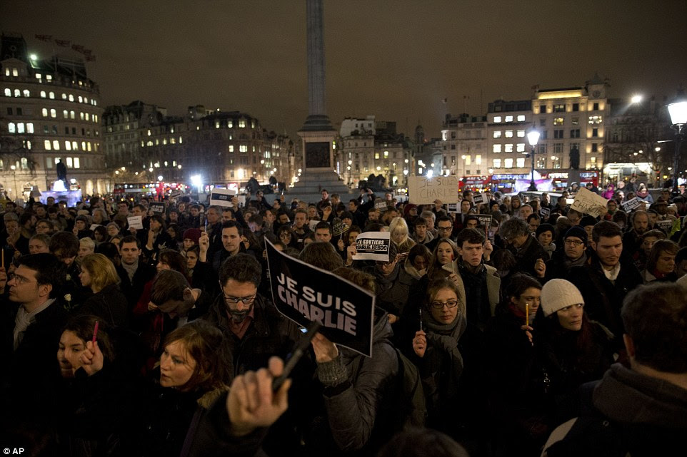 Standing together: People hold up pens and posters reading 'I am Charlie' in French as they take part in a vigil in Trafalgar Square, London