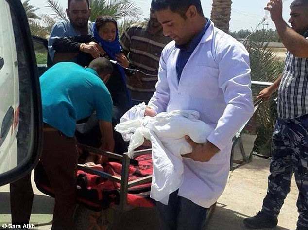 Innocent: It is claimed this baby was delivered in the open air to a Sunni woman who was one of thousands not allowed to cross the Bzabz bridge  - a key entry route to Baghdad less than 40 miles away