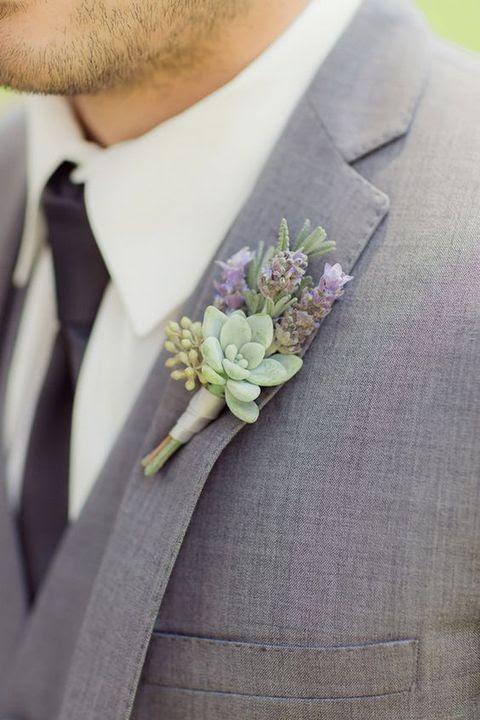 ein grauer Hochzeitsanzug mit einem saftigen und Lavendel Ansteckblume und eine schwarze Krawatte sieht wow