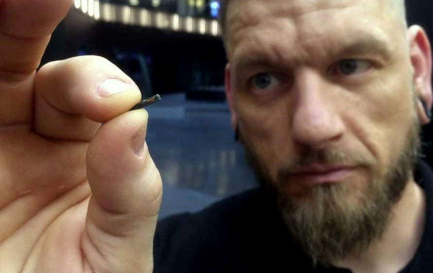 """Self-described """"body hacker"""" Jowan Osterlund from Biohax Sweden, holds a small microchip implant, similar to those implanted into workers at the Epicenter digital innovation business centre during a party at the co-working space in central Stockholm, Tuesday March 14, 2017. (Photo: James Brooks/AP)"""