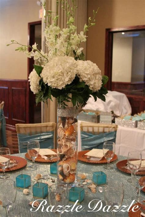 Centerpiece vase filled with sea shells. Beach theme