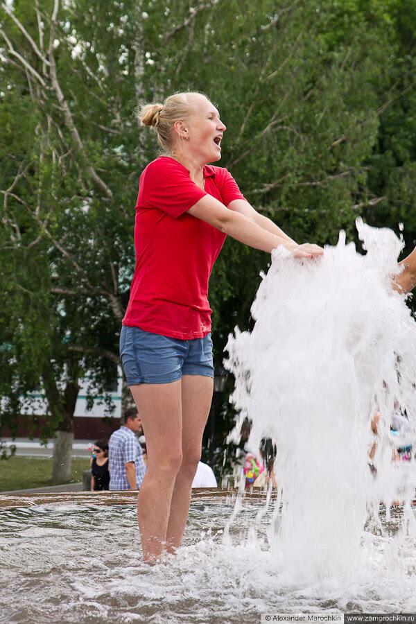 Девушка в одежде купается в фонтане
