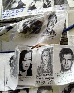 Una mujer cuelga fotografías de desaparecidos durante la última dictadura militar, alrededor de la Piramide de Mayo frente a la Casa de Gobierno, en Buenos Aires, Argentina, el 10 de diciembre de 2003, cuando se cumplen 20 años del retorno de éste país a