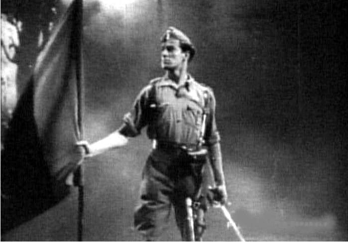 Fotograma de la película propagandística Rojo y negro (1942) en la que un soldado de uniforme porta la bandera falangista. Imagen: CEPICSA.