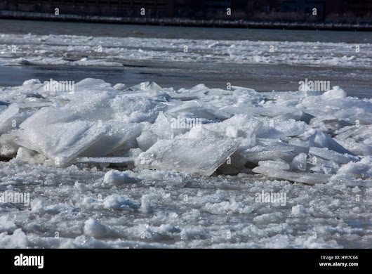 Stock Photo - Frozen, snow capped ice blocks floating down the river on a cold winter afternoon