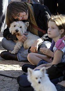 Una mujer abraza a su perro durante el concierto. | AP