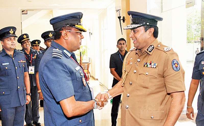 Air Force Commander Air Marshal Kapila Jayampathy greets the Inspector General of Police.