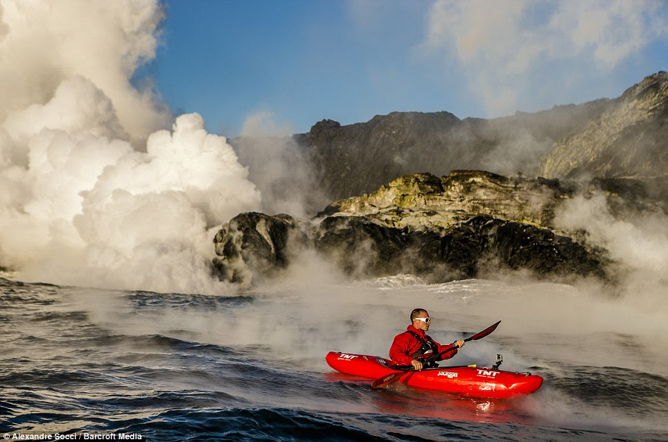 Brave: Pedro Oliva is immersed in steam as he paddles feet from molten lava flows in Kauai, Hawaii