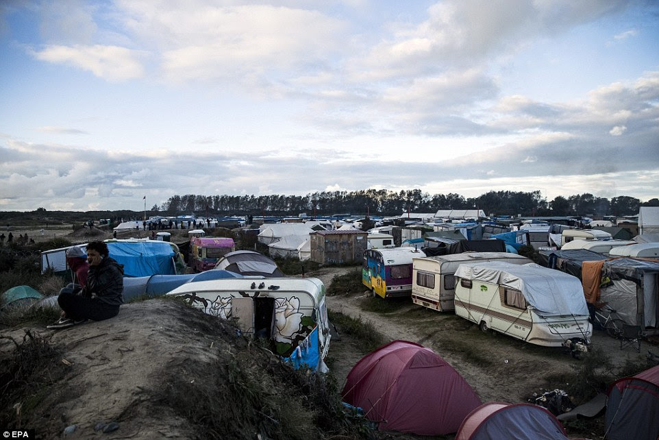 Migrants sit on top of a small hill to make a phone call in the 'Jungle' camp in Calais, France
