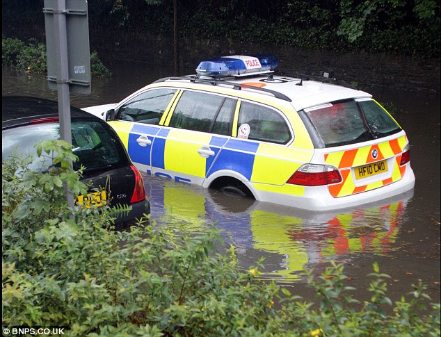 Going nowhere: Water laps up to the doors of a police car as it lies stranded in the rainwater