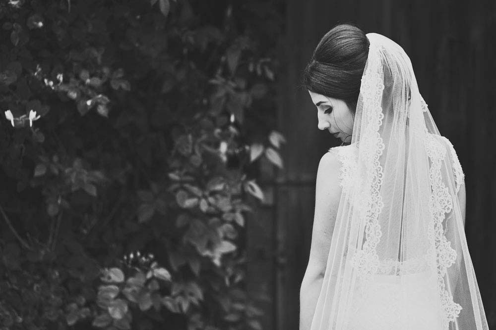 black & white photo of bride looking over her shoulder - www.helloromance.co.uk