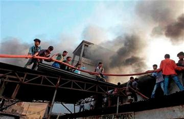 (AP Photo/A.M. Ahad). Bangladeshi firefighters and volunteers work to douse a fire at a two-storied garment factory in Dhaka, Bangladesh, Saturday, Jan.26, 2013.