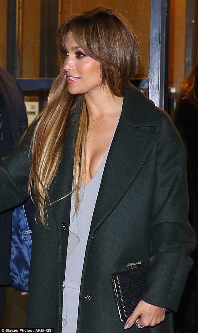 Ela exibia sua clivagem em um vestido cinza baixo sob um casaco de inverno escuro.