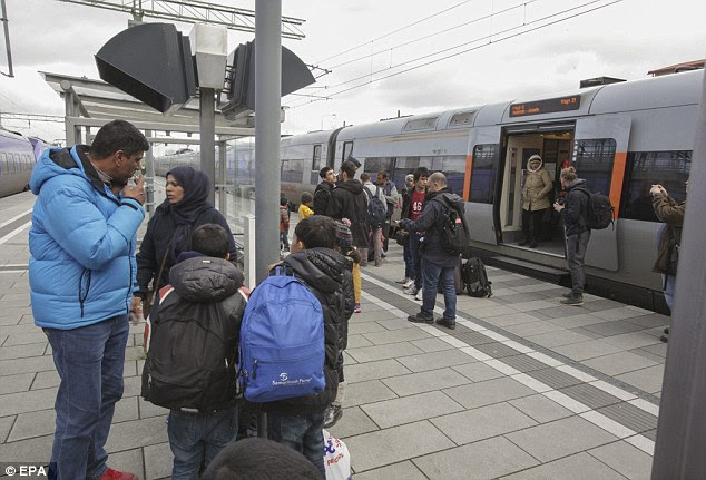 A group of migrants from arrive off a train at the Swedish end of the bridge between Sweden and Denmark