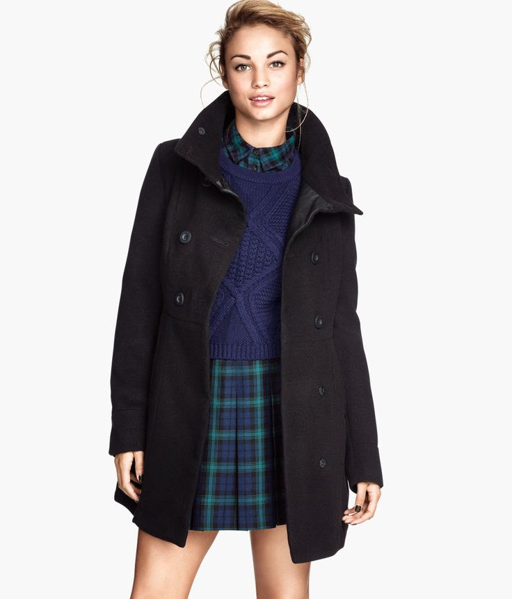 Black felted double-breasted coat with high collar and side pockets, paired with a plaid pleated skirt and pattern-knit sweater.│ H&M Divided