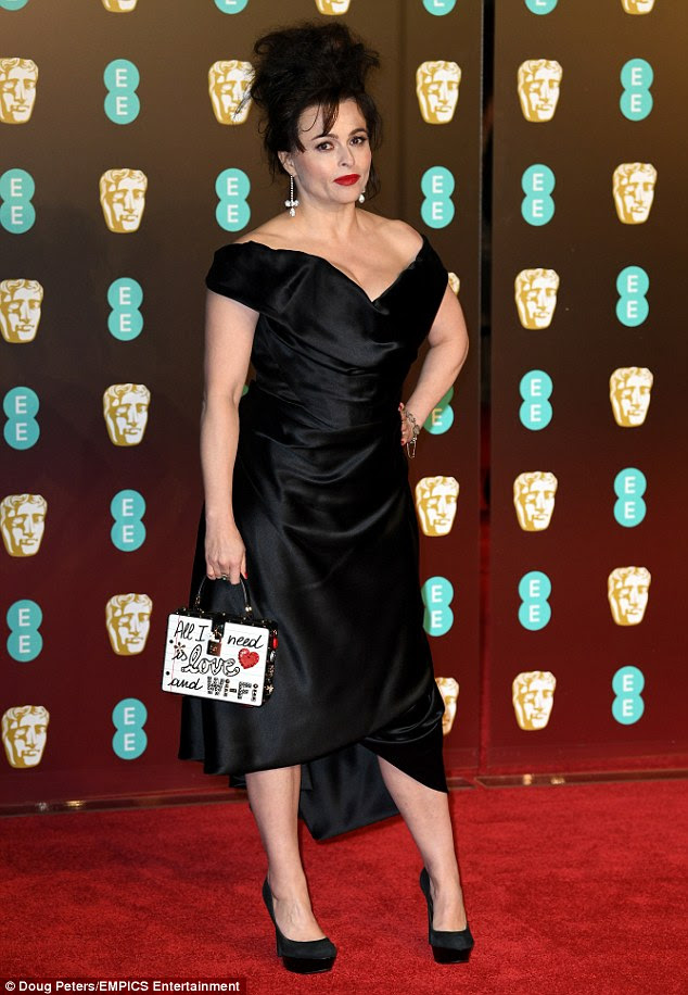 Glamour:Her brunette tresses were styled into a messy updo with strands framing her face while her make-up look featured fluttery lashes, liner and a slick of red lipstick
