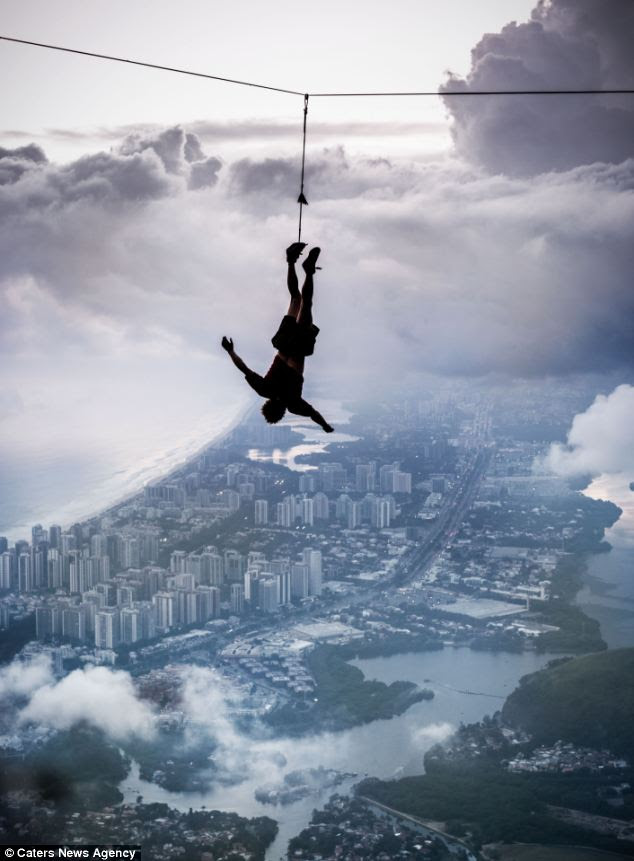 Hanging around: Andy Lewis hangs upside down over the Rio skyline while tied only by his ankle