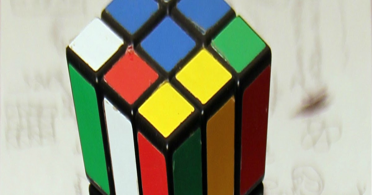 Anamorphic illusions of Rubiks cube, a roll of tape, and a