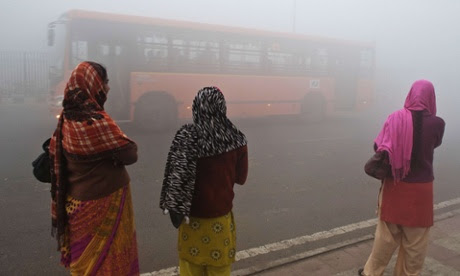 In the city of Delhi, commuters wait for a bus early on a polluted morning.