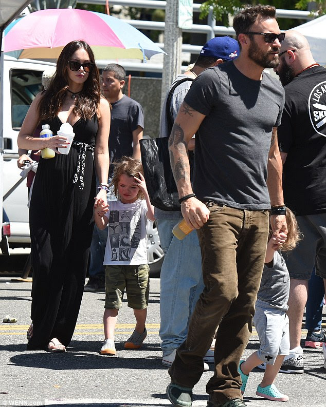 Laid-back maternity style: Megan wore a black maxi dress with a belt above the waist, along with flip flops