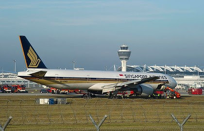 The Singapore Airlines Boeing 777 is surrounded by rescue personnel after it slid off the runway at Munich airport.