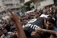 Palestinians carry the body of militant Basel Ahmed during his funeral in al-Bureij refugee camp in the central Gaza Strip. (AFP Photo/Said Khatib)