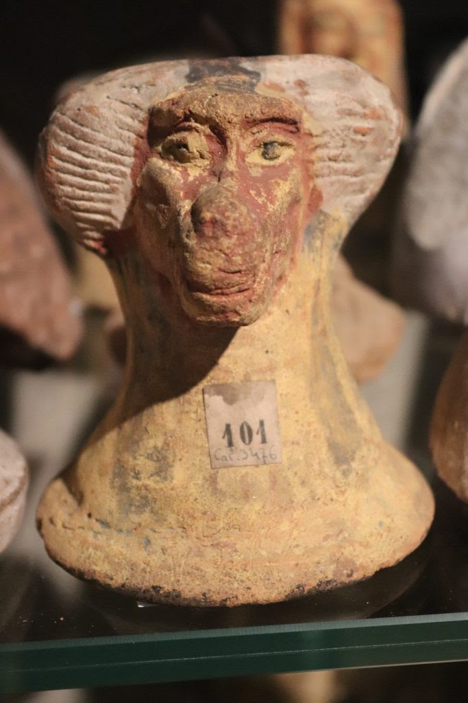 Painted clay canopic jar lid showing the baboon-headed            god Hapy who protected the lungs of the deceased amongst a            display of canopic jar lids